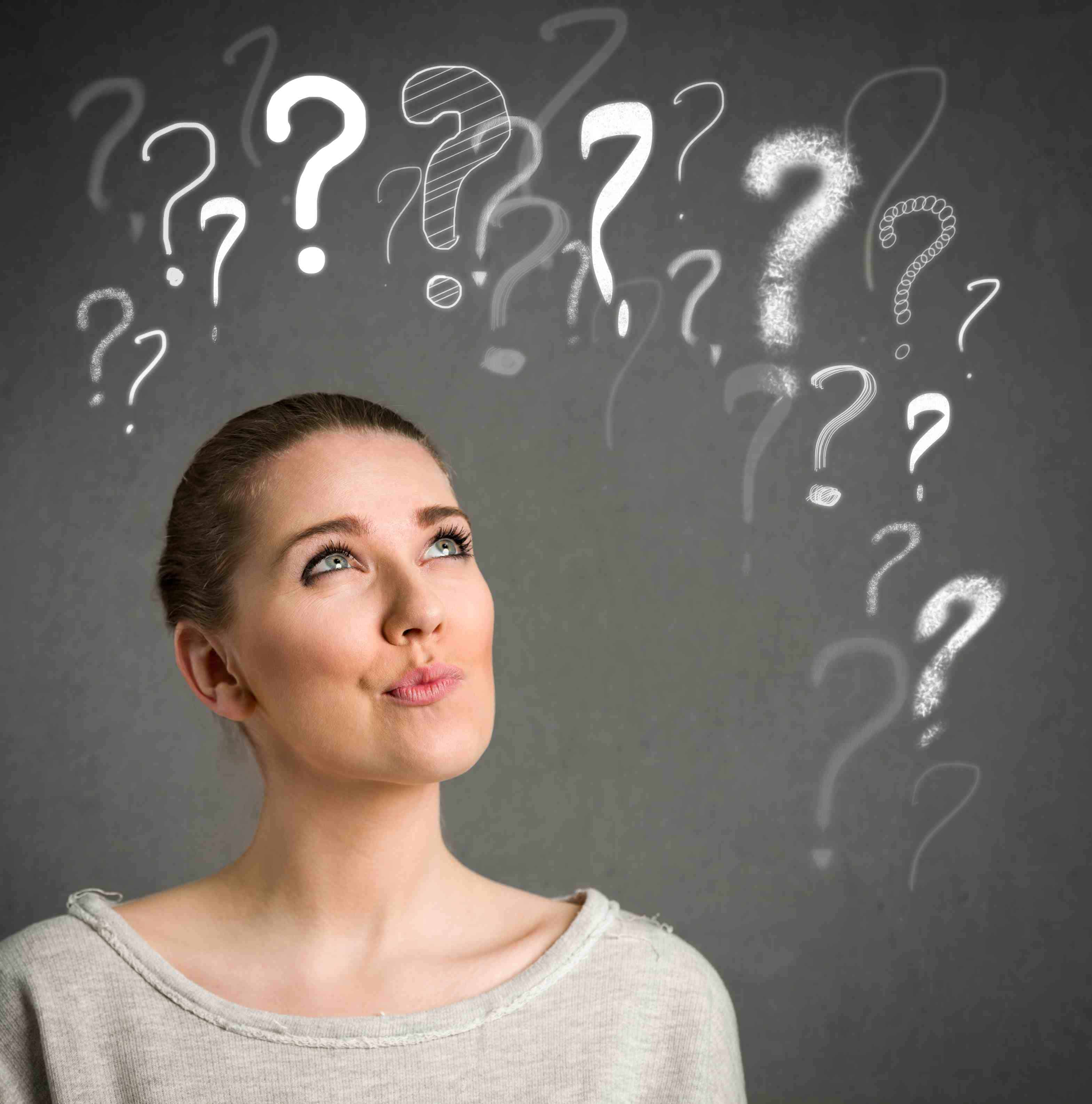 Young woman makes a face and thinking with question marks over head
